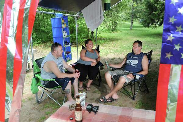 Memorial Day weekend campers, from left, Jay and Sarah Brassard of Rotterdam and Cole VanDerlinden of Burnt Hills enjoy some drinks in the shade of their canopy at Thompson's Lake State Campground on Friday, May 27, 2016 in New Scotland, N.Y. (Lori Van Buren / Times Union)