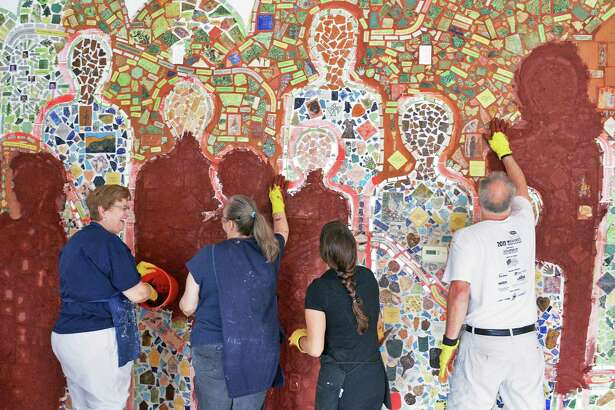 Artist/members finish work on The Wall Memorial, a permanent mosaic installation made of ceramic tiles representing memories of artistic achievements and experiences at the Roarke Center Friday May 28, 27, 2016 in Troy, NY.  (John Carl D'Annibale / Times Union)