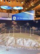 Conference-goers look at a model wind farm at the General Electric Renewable Energy booth at the American Wind Energy Association annual conference in New Orleans on May 24, 2016. Congress will phase out tax credits for wind energy projects over the next four years, forcing the industry to compete without subsidies.