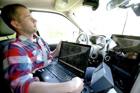 Elliot Johnson holds a computer keyboard while a self-driving Ford Explorer goes around the test track at Southwest Research Institute in San Antonio. Engineers work on developing autonomous vehicles for everyone from the U.S. military to farmers.