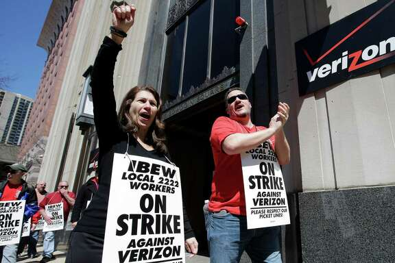 Verizon workers picket outside a company facility in Boston last month. The company and unions reached an agreement in principle Friday. Verizon released a statement saying it's pleased with the deal.