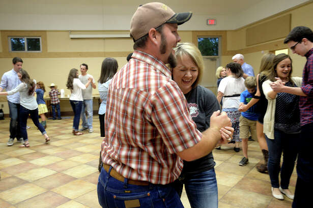 Adam and Amanda Jeffcoat laugh as they join others in a new step at the Old Fashion Barn Dance held Friday night in the community center at Rogers Park. Attendees learned traditional contra style dances, led by caller Michelle Ozmun, as they spun their partners, sashayed, and circled their way through the center. Photo taken Friday, May 27, 2016 Kim Brent/The Enterprise