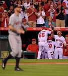 Los Angeles Angels' Kole Calhoun (56) is congratulated by teammates after scoring on a double by Mike Trout as Houston Astros starting pitcher Mike Fiers, foreground, walks back to mound during the third inning of a baseball game, Friday, May 27, 2016, in Anaheim, Calif. (AP Photo/Mark J. Terrill)