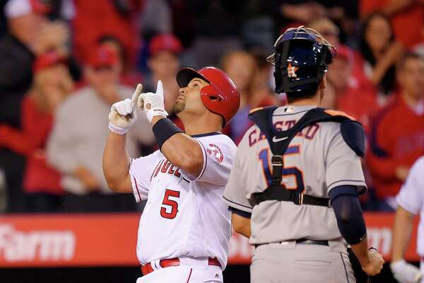Los Angeles Angels' Albert Pujols, left, points skyward after hitting a two-run home run as Houston Astros catcher Jason Castro stands by during the third inning of a baseball game, Friday, May 27, 2016, in Anaheim, Calif. (AP Photo/Mark J. Terrill)