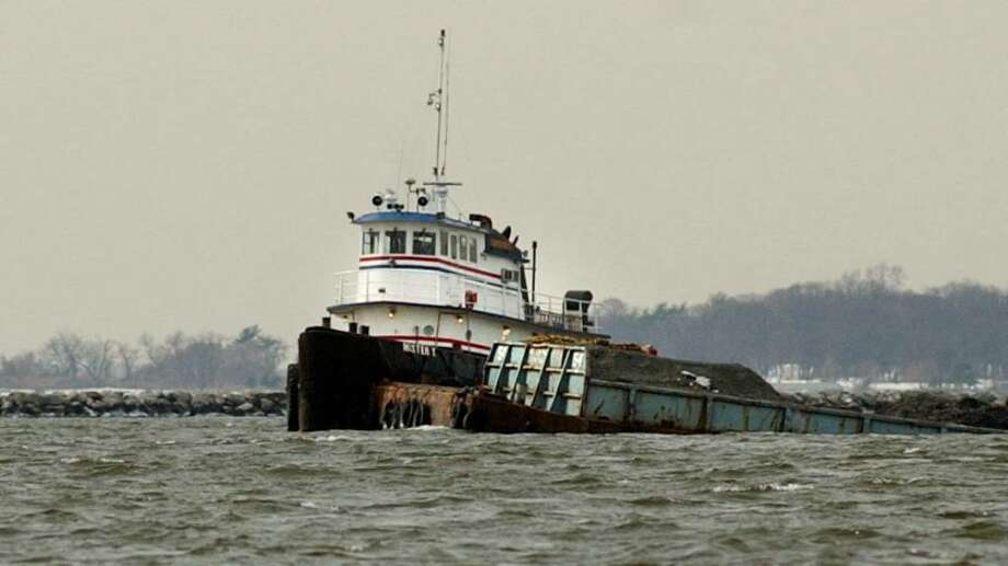 A tug sits next to a barge that started to sink in Stamford Harbor. Photo: File Photo / Stamford Advocate File Photo