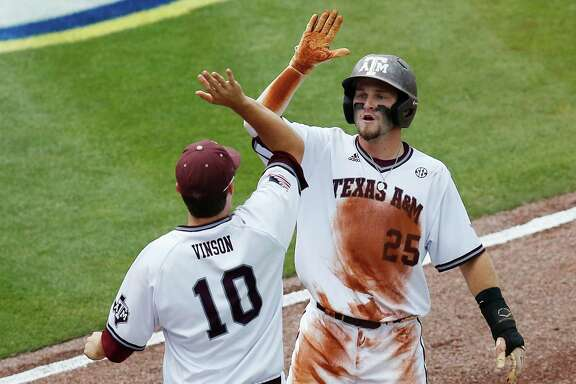 Texas A&M's Austin Homan, right, high-fives teammate Andrew Vinson after scoring one of the Aggies' seven first-inning runs against Vanderbilt in the Southeastern Conference tournament Friday at Hoover, Ala.