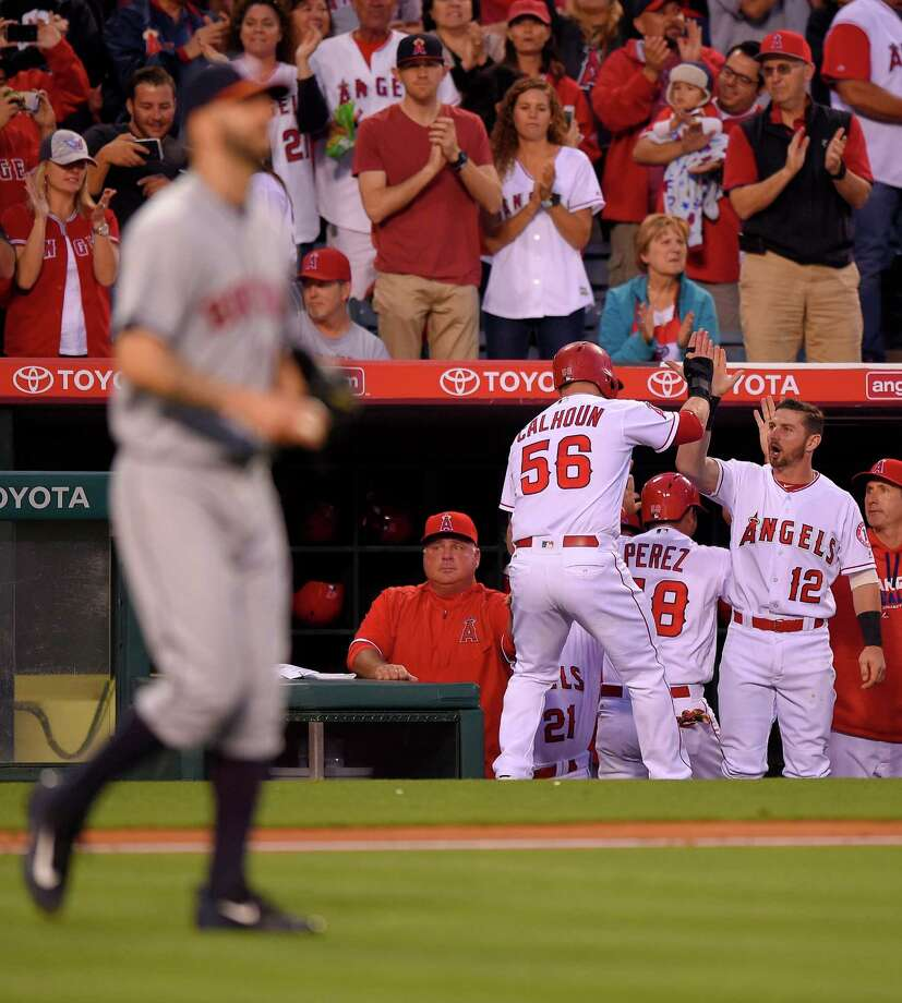 Los Angeles Angels' Kole Calhoun (56) is congratulated by teammates after scoring on a double by Mike Trout as Houston Astros starting pitcher Mike Fiers, foreground, walks back to mound during the third inning of a baseball game, Friday, May 27, 2016, in Anaheim, Calif. (AP Photo/Mark J. Terrill) Photo: Mark J. Terrill, STF / Copyright 2016 The Associated Press. All rights reserved. This material may not be published, broadcast, rewritten or redistribu