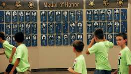 Kids on school trip takes pictures at the Above and Beyond: Medal of Honor in Texas display at the State Capitol in Austin on May 26, 2016.