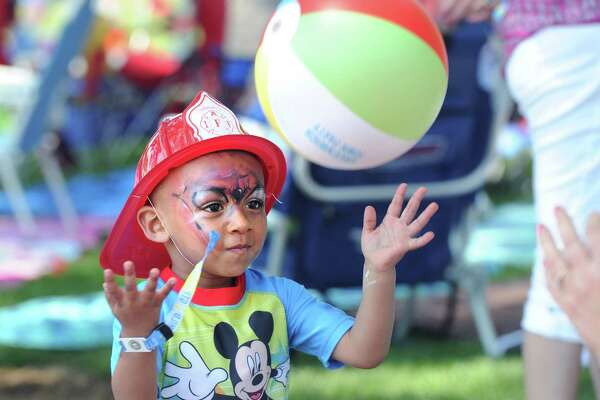C.J. Pierce, 2, of Greenwich, throws a beach ball during the Greenwich Town Party at Roger Sherman Baldwin Park in Greenwich, Conn., Saturday, May 28, 2016.