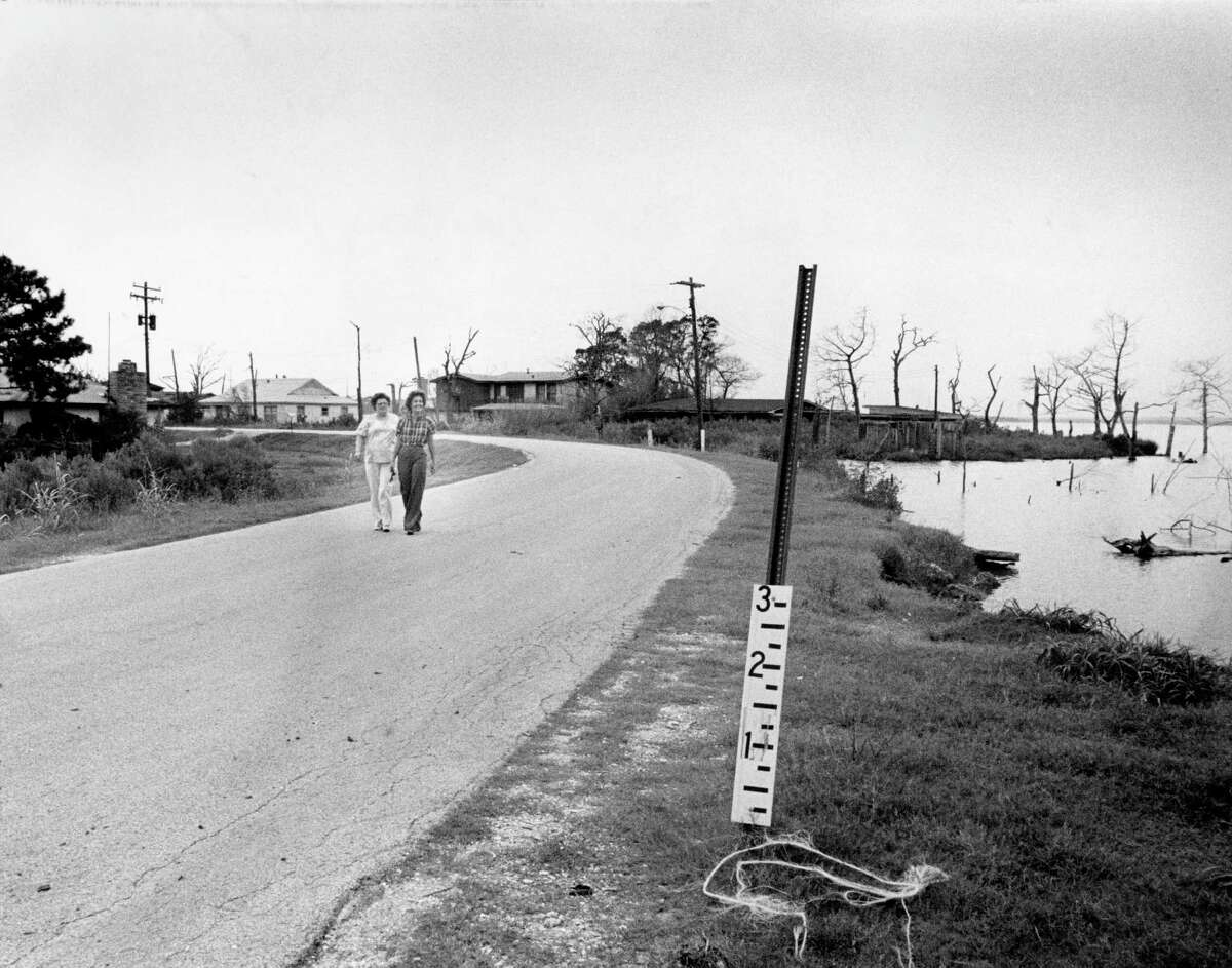 08/10/1979 - (L-R) Jean Shepherd and Susie Brown, residents of the Brownwood Subdivision in Baytown, walk the area's perimeter road as bay waters lap just a few feet away. In heavy rains, the water level climbs up the roadside gauge and isolates the area from outsiders.