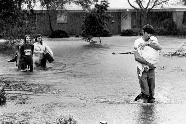 06/1981- Charles Combs carries his baby through rainwater to higher ground as he and his family leave their home in the flooded Brownwood Subdivision in Baytown. His wife, Moselle, carries a uitcase and leads their other children to safety. Many residents in the area evacuated for higher ground after a tropical depression in the Gulf of Mexico caused heavy rains.The Combs family came to Baytown a year agro from Kentucky.