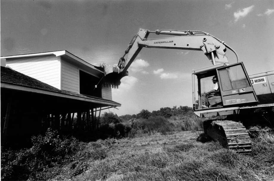 07/30/1985 - Ray Herrin tears down a house on Cobaniss Street in the Brownwood Subdivision in Baytown. Property in the flood-ravaged subdivision was condemned following damage from Hurricane Alicia. Baytown City Council hired Olshan Inc. of Houston to clear the lots to make way for a park. Photo: Howard Castleberry, © Houston Chronicle / Houston Chronicle