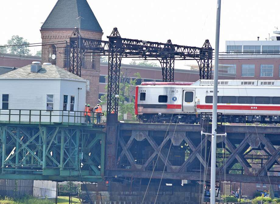 A train headed toward Grand Central Terminal slowly passes bridge maintenance workers on Walk bridge at 4:20 p.m. It was one of the first trains to cross the bridge since two tracks on it were reopened to service. Photo: Harold F. Cobin