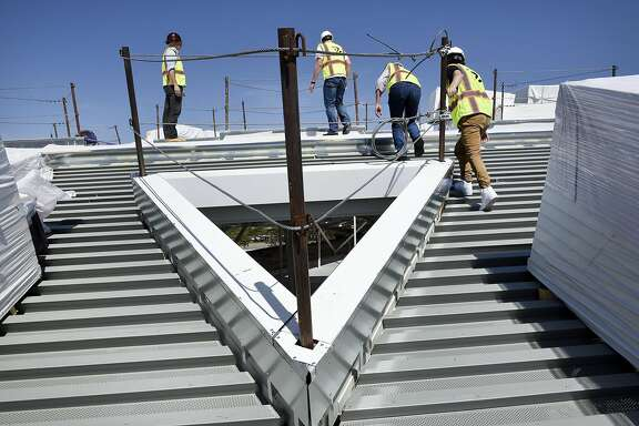 Guests walk past triangle shaped sky lights on the roof during a tour of NVIDIA's new triangle shaped building that is under construction in Santa Clara, CA Friday, May 27th, 2016. The futuristic triangle shaped building was designed by architects are using NVIDIA's own 3D rendering Iray virtual reality technology.