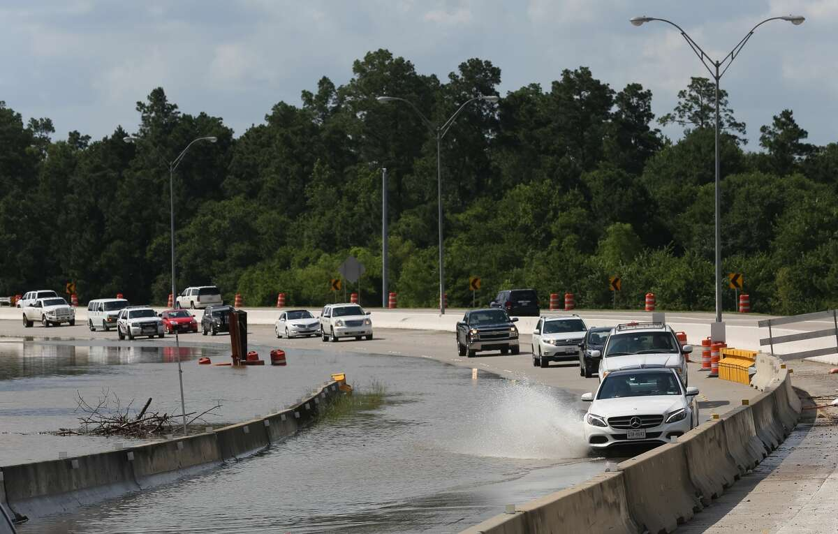 Rising flood waters begin to cover a section of the Hardy Toll Road where it meets the Grand Parkway, Saturday, May 28, in Spring.