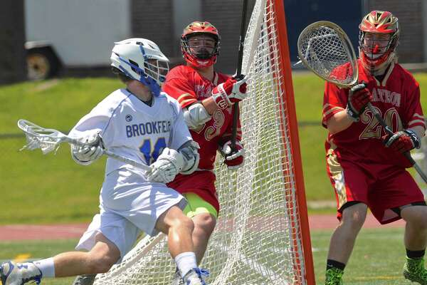 Brookfield's Harrison Manesis (10) circles around the back of the Stratford net while being defended by Jack Branco (23) and Goalie Dan Cox (20) in the state class M boys lacrosse game between Stratford and Brookfield high schools, on Saturday, May 28, 2016, at Brookfield High School, Brookfield, Conn.