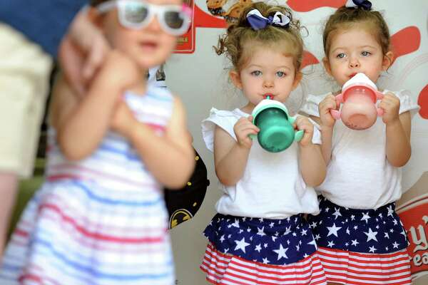 Two-year-old twins Scarlett Rose, center, and Piper Renea Baranowski of Clifton Park sip melting, mint chocolate chip ice cream from cups as they wait for the Memorial Day Parade on Saturday, May 28, 2016, in the Village of Lake George, N.Y. (Cindy Schultz / Times Union)