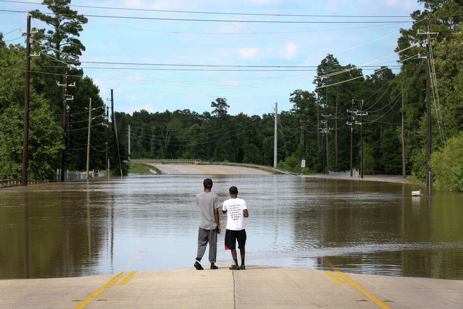 David Rhodes and his brother Derek look at rising flood waters from Spring Creek, along Riley Fuzzel Road, Saturday, May 28, 2016, in Spring. The pair, both musicians, came from San Antonio to visit their uncle.