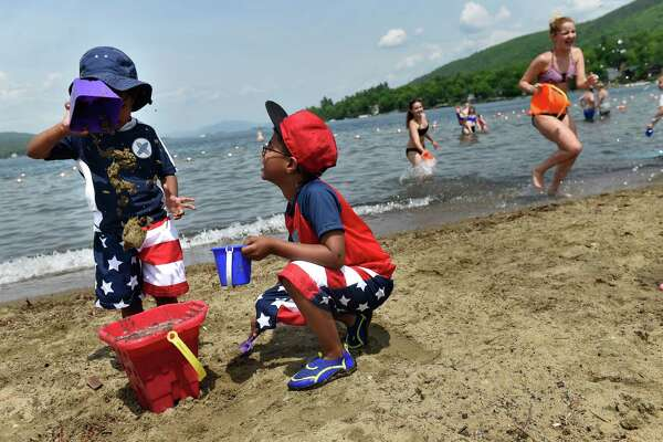Jason Latchminarain, 3, left, of Schenectady and his brother Joshua Latchminarain, 6, add sand and water to a bucket as they play on Saturday, May 28, 2016, at Million Dollar Beach in the Village of Lake George, N.Y. It was opening day for the summer season at the beach. (Cindy Schultz / Times Union)