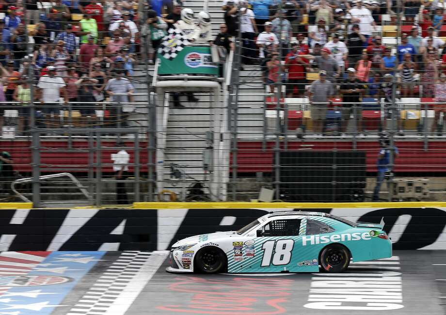 Denny Hamlin takes the checkered flag to win the NASCAR Xfinity series race at Charlotte Motor Speedway on Saturday. Photo: Chuck Burton, Associated Press