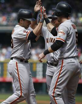 San Francisco Giants' Buster Posey, left, is congratulated by Gregor Blanco, back right, and Matt Duffy after hitting a three-run home run off Colorado Rockies starting pitcher Eddie Butler in the first inning of a baseball game Satuday, May 28, 2016, in Denver. (AP Photo/David Zalubowski)