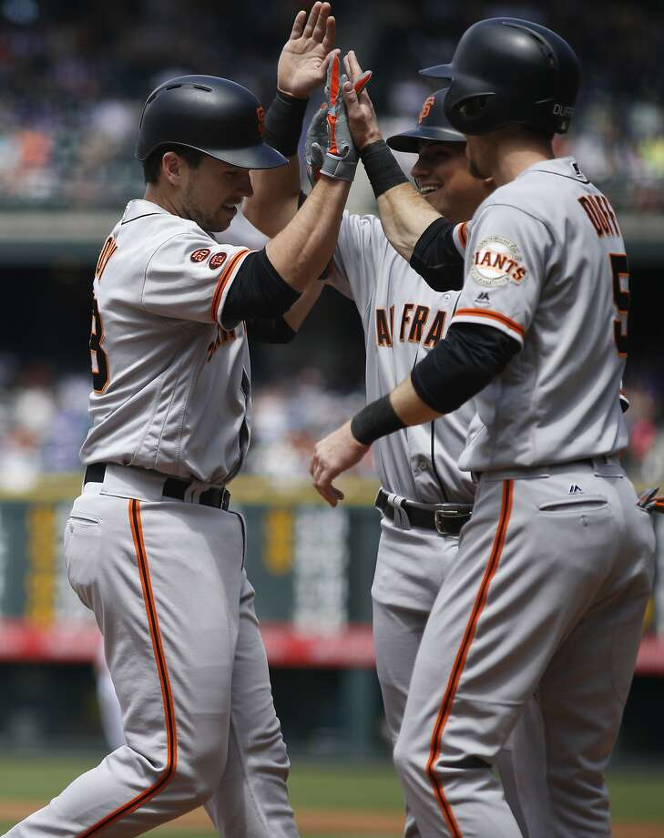 San Francisco Giants' Buster Posey, left, is congratulated by Gregor Blanco, back right, and Matt Duffy after hitting a three-run home run off Colorado Rockies starting pitcher Eddie Butler in the first inning of a baseball game Satuday, May 28, 2016, in Denver. (AP Photo/David Zalubowski) Photo: David Zalubowski, Associated Press