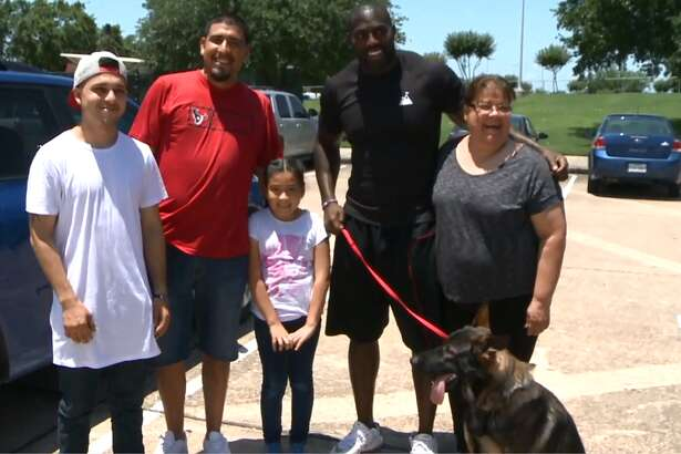Whitney Mercilus with the Barrera family after they returned his dogs to him.