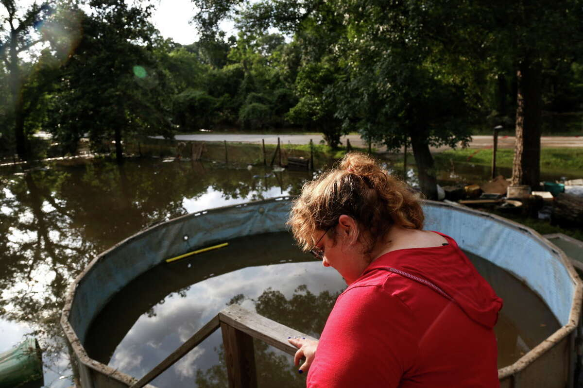"""Hazel Smith looks out at her flooded property Saturday, May 28, 2016, in Tomball. The home, which sits at least two feet off the ground, had at least two feet of water in it the night before. """"I've been staying with neighbors I'd never met before the flood,"""" she said. """"I honestly don't care about the material things, but it's all that hard work."""" Smith said she works two jobs."""