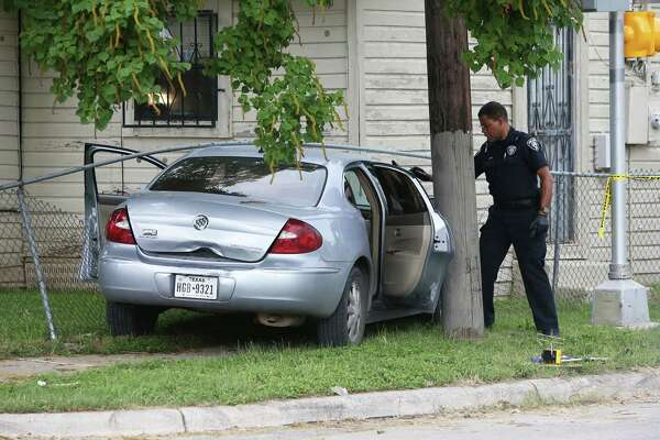 An officer examines car doors on a crashed car at the scene of a shooting at North Gevers and Blue Bonnet on May 28, 2016.