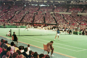 ** FILE ** Bobby Riggs, right, goes after a quick shot by Billie Jean King in the winner-take-all tennis match in the Astrodome in Houston, in this Sept. 20, 1973 photo. The Astrodome, the famed landmark that helped put Houston on the map four decades ago, still stands, but not very proudly. It is an afterthought of this Super Bowl week, a run-down relic, dwarfed by the neighboring new Reliant Stadium in both dimension and prestige. (AP Photo)