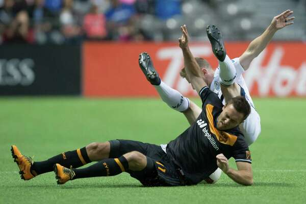 Vancouver Whitecaps' Jordan Harvey, back, falls over Houston Dynamo's Andrew Wenger during the first half of an MLS soccer game in Vancouver, British Columbia, Saturday May 28, 2016. (Darryl Dyck/The Canadian Press via AP)