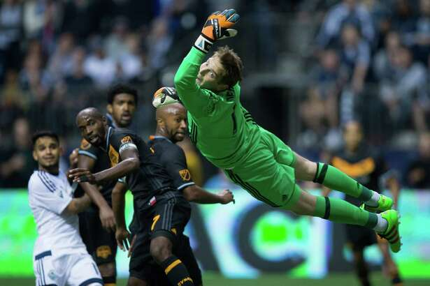 Houston Dynamo goalkeeper Tyler Deric, right, watches the ball roll out of bounds after making a diving save against the Vancouver Whitecaps during the second half of an MLS soccer game in Vancouver, British Columbia, Saturday May 28, 2016. (Darryl Dyck/The Canadian Press via AP)