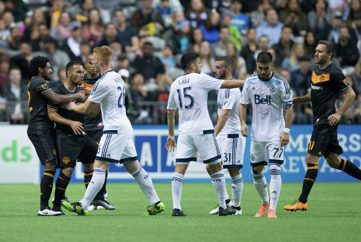 Houston Dynamo's Alex, second left, and Vancouver Whitecaps' Pedro Morales, second right, are separated by their teammates after both received red cards during the first half of an MLS soccer game in Vancouver, British Columbia, Saturday May 28, 2016. (Darryl Dyck/The Canadian Press via AP)