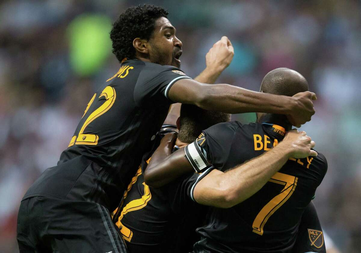 Houston Dynamo's Sheanon Williams, from left, Will Bruin and DaMarcus Beasley celebrate Beasley's goal against the Vancouver Whitecaps during the first half of an MLS soccer game in Vancouver, British Columbia, Saturday May 28, 2016. (Darryl Dyck/The Canadian Press via AP)