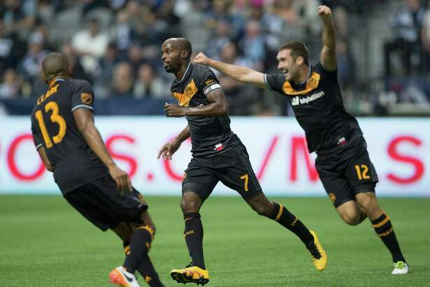 Houston Dynamo's Ricardo Clark, from left, DaMarcus Beasley and Will Bruin celebrate Beasley's goal against the Vancouver Whitecaps during the first half of an MLS soccer game in Vancouver, British Columbia, Saturday May 28, 2016. (Darryl Dyck/The Canadian Press via AP)
