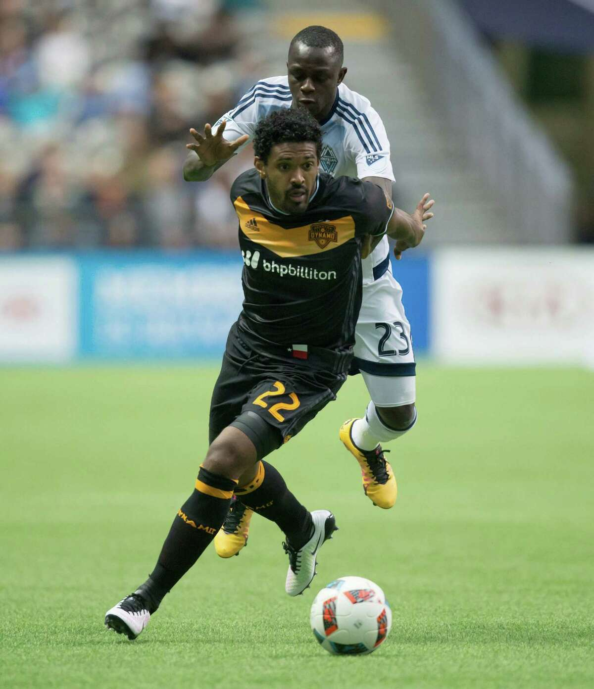 Houston Dynamo's Sheanon Williams, front, fights off Vancouver Whitecaps' Kekuta Manneh as he moves the ball during the first half of an MLS soccer game in Vancouver, British Columbia, Saturday May 28, 2016. (Darryl Dyck/The Canadian Press via AP)