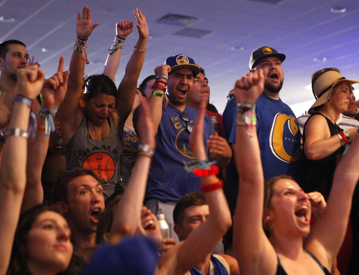 Festival goers cheer while watching the NBA Conference Finals against Oklahoma City Thunder at the Bottle Rock 2016 festival in Napa, Calif. on Saturday, May 28, 2016.