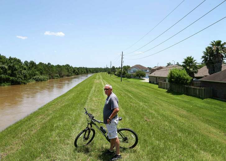 "Tim Bowlin checks the water level in Spring Creek, in the Northwood Pines subdivision on Saturday in Spring. The water level in the creek is rising, and it was expected to crest that night. ""I've been here 15 years, and I've never seen anything like this,"" he said."