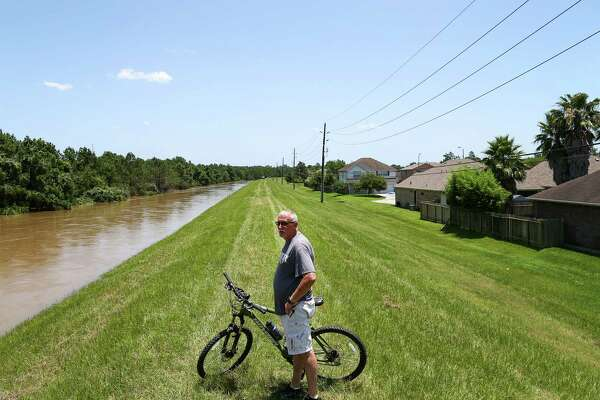 """Tim Bowlin checks the water level in Spring Creek, in the Northwood Pines subdivision on Saturday in Spring. The water level in the creek is rising, and it was expected to crest that night. """"I've been here 15 years, and I've never seen anything like this,"""" he said."""