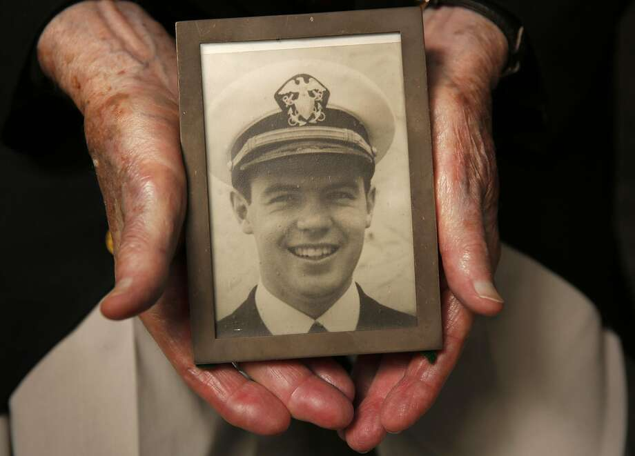 Thomas Cooney holds a photo of himself as a World War II Navy lieutenant. He served on a D-Day landing boat. Photo: Leah Millis, The Chronicle