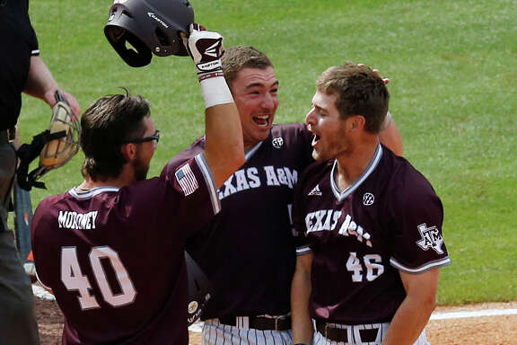 Texas A&M's Walker Pennington, right, celebrates with teammates Jonathan Moroney, center, and Michael Barash after hitting a three-run homer Saturday.