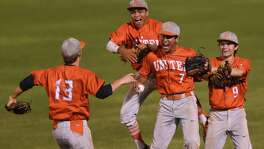 Laredo United players mob teammate Jorge Ramos (7) after he caught a fly ball to win a decisive 4-1 Game 3 over Holmes.