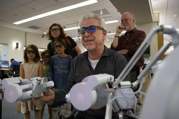 (left to right) Harriet Won, 7, Anders Nystol,7, Julius Won, 9, Andrea Won and Professor Kenneth Salisbury early watch as Stanford professor Oussama Khatib (front center) demonstrates how to use the haptic devices that control Ocean One while  at Stanford University on Friday, May 27, 2016.