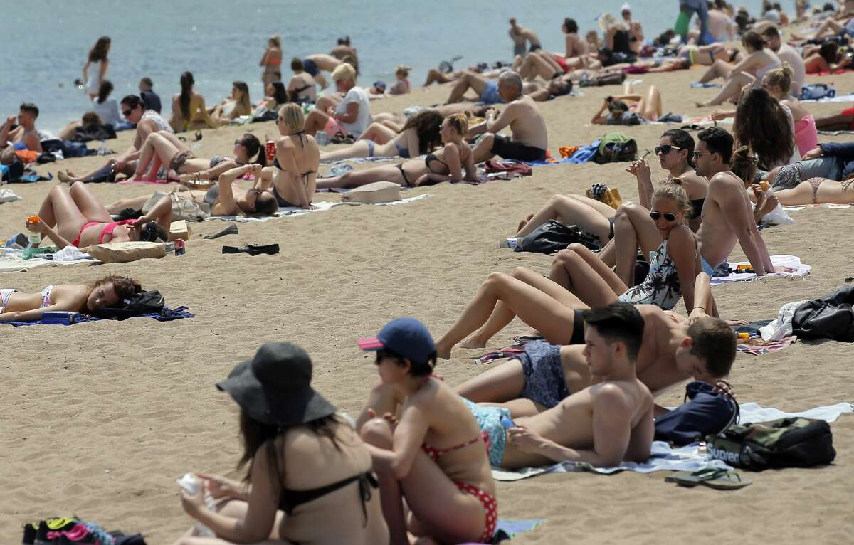 In this Wednesday, May 25, 2016 photo, people sunbathe at the Barceloneta beach in Barcelona, Spain. With sunny days getting longer and lazier, sparkling beaches warming up and terrorism fears driving customers away from other Mediterranean destinations, Spain and Portugal are reaping an economic bonanza from tourism. (AP Photo/Manu Fernandez)