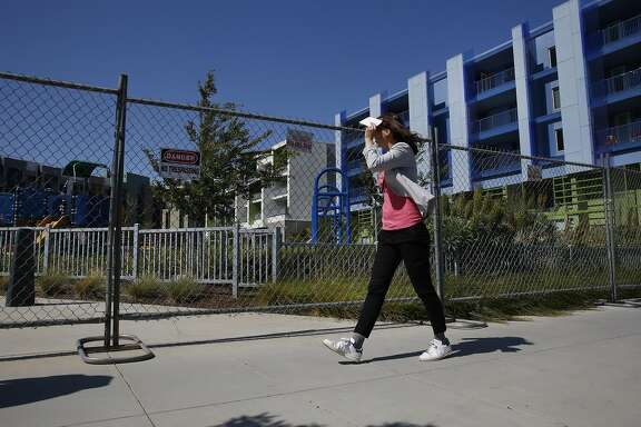A woman walks past the Mission Bay Children's Park as it sits empty May 27, 2016 in San Francisco, Calif.
