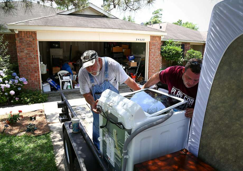 Fred Schaefer (left) helps his son Tony Dotson load belongings as they evacuate from Spring, Texas. Photo: Jon Shapley, Associated Press
