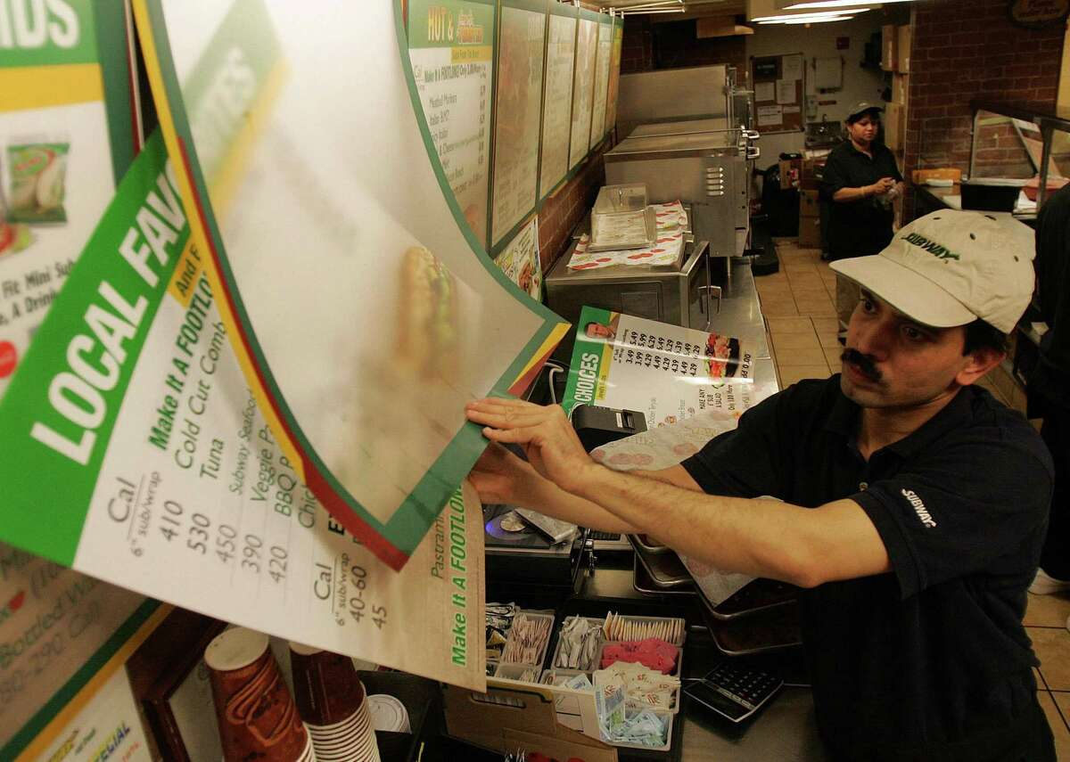 Amin Chakma puts up new menus featuring calorie counts at a New York Subway restaurant in 2007. Because nationwide labeling laws are still relatively new, the scientific jury is still out on whether posting calories will help people make better food decisions.