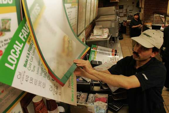Amin Chakma puts up menus featuring calorie counts at a Subway restaurant. The FDA released a final rule earlier this month that requires restaurant chains of a certain size to include calorie information on their menus. Some big chains have already modified their menus in anticipation of the new rule, but many smaller chains are just starting to get new menus ready.