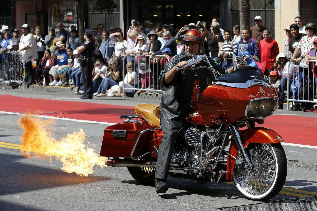 A motorcyclist shoots flames out of his tail pipe during the annual Carnaval parade in San Francisco, California, on Sunday, May 29, 2016.