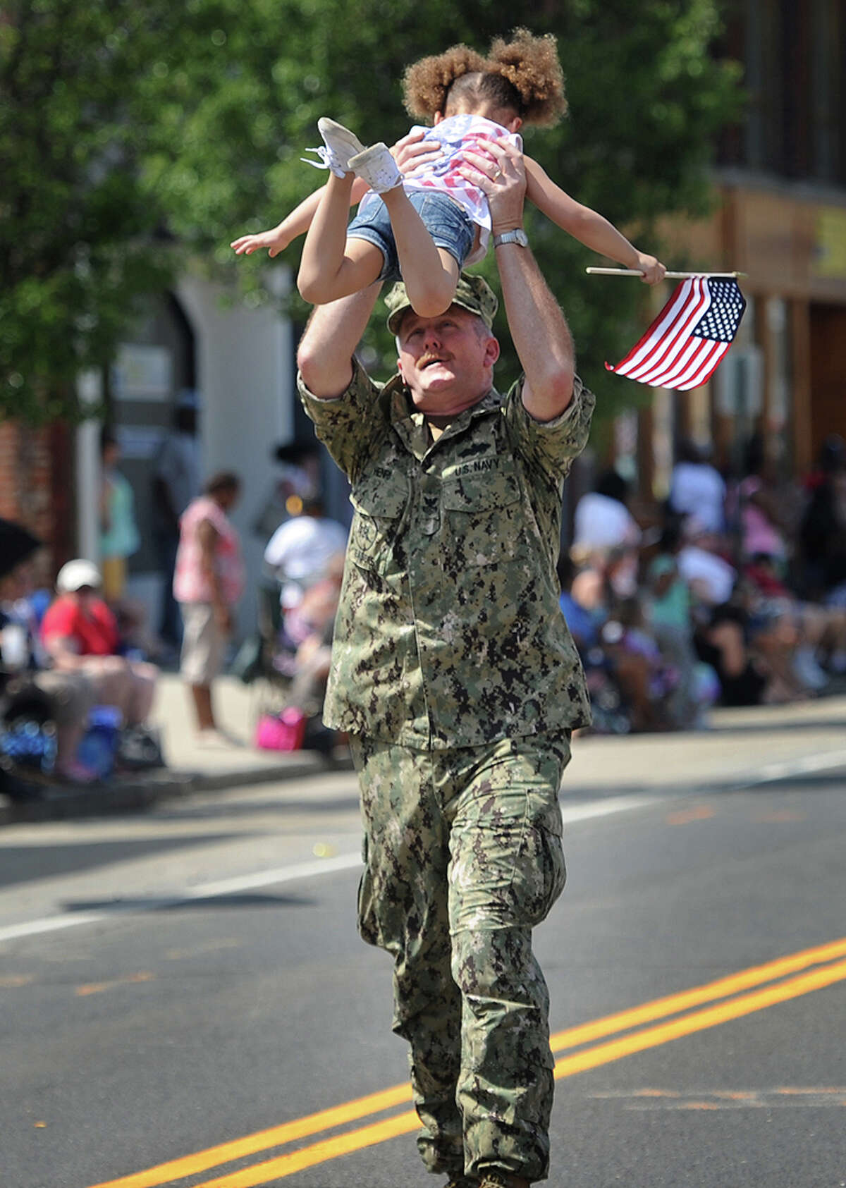 Navy veteran Thomas Henri, of Ansonia, is greeted by his granddaughter Justice Dukes, 3, as he marches in the Memorial Day parade on Main Street in Ansonia, Conn. on Sunday, May 29, 2016.